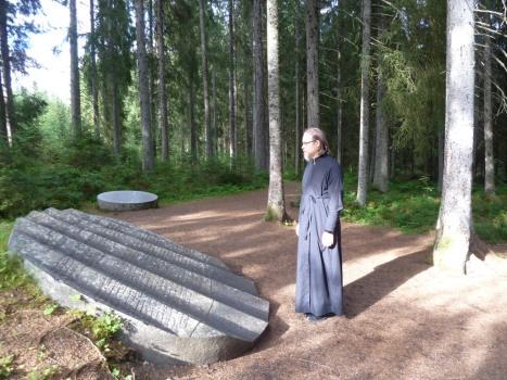 У памятной плиты на месте расстрелов концлагеря в лесу Фаллстада
