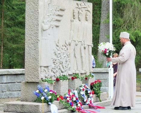 Возложение священником цветов к памятнику узникам Фалстада